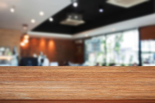 Top of wooden table with blurred cafe interior for background. product display template