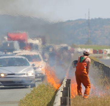 A road worker is putting up a fire caused traffic jam on a highway.