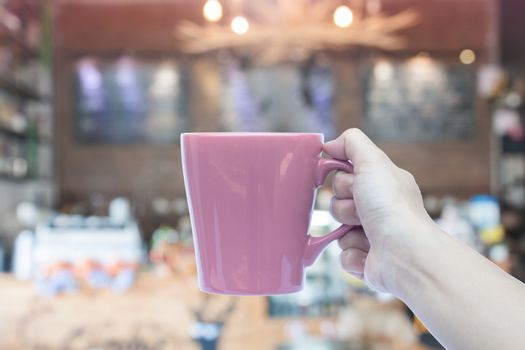 Woman holding coffee mug with blurred cafe background, stock photo