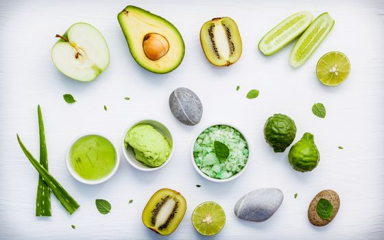 Homemade skin care and body scrubs with green natural ingredients aloe vera ,lime,cucumber ,aromatic salt ,green apple,mint ,rosemary ,kiwi and sage set up on white wooden background with flat lay.