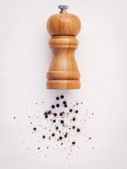 Close up of bottle black pepper mill on white wood table. Season