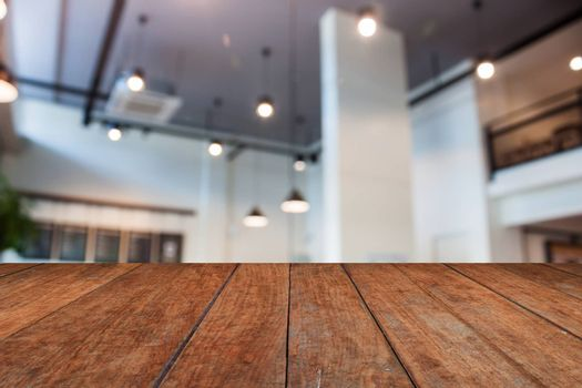 Brown wooden table top with abstract blur coffee shop interior for background