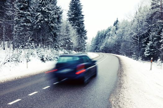 Lonely car in motion blur on the road in winter landscape