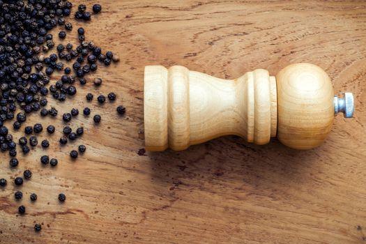 Close up of bottle black pepper mill on teakwood table. Seasonin