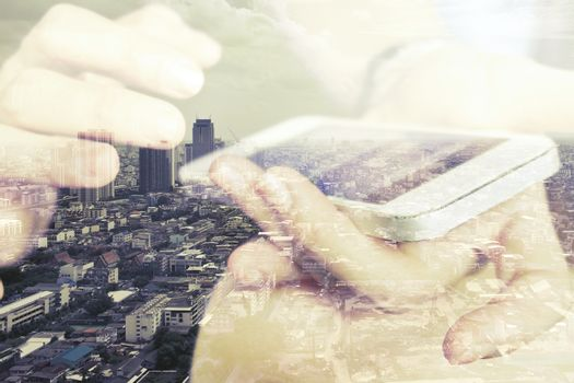 Double exposure of using smart phone and cityscape background ,Business technology concept.