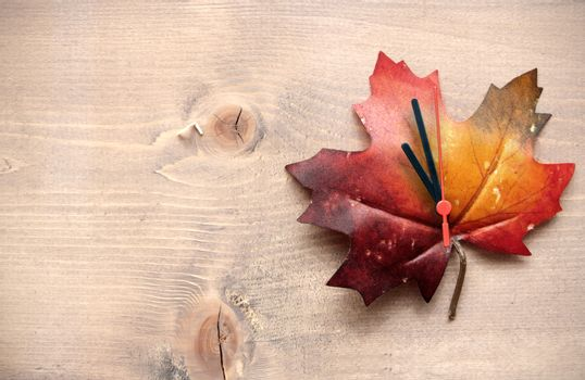 Autumn leaf with clock hands on top of a wooden background