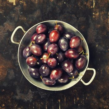 Plums in a bowl on a rural background
