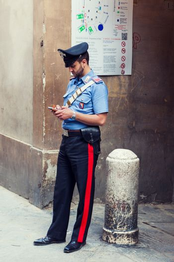 SIENA, ITALY - JUNE 29, 2016: Italian policeman standing on the street and checking his smartphone in Siena, Italy