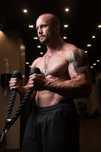 Muscular Man Exercising Biceps On Cable Machine