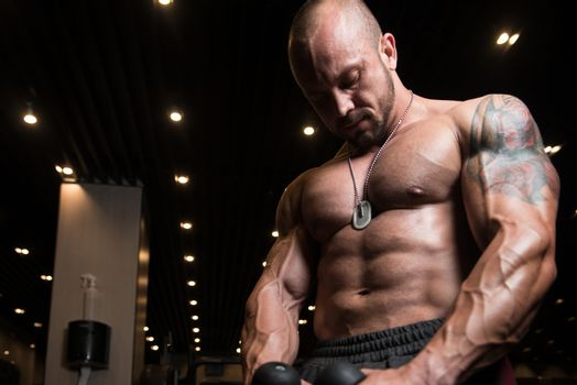 Man Doing Exercise For Biceps On Cable Machine