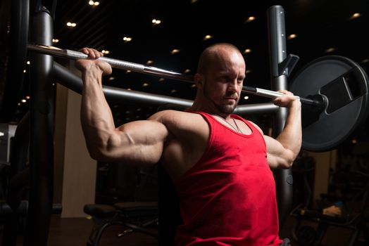 Muscular Man Doing Heavy Weight Exercise For Shoulders