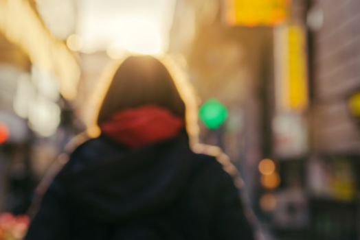 Blur image of unrecognizable female person on the street
