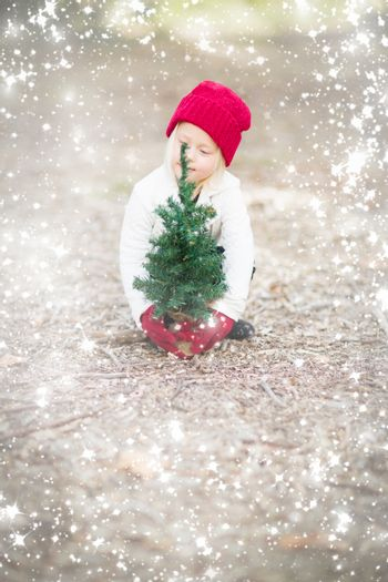 Baby Girl In Red Mittens and Cap Near Small Christmas Tree Outdoors with Snow Effect.
