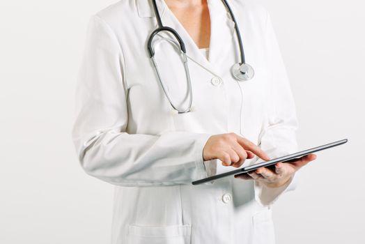 Female general medical practitioner using tablet computer