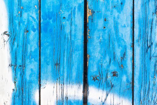 Blue painted wooden planks peeling off