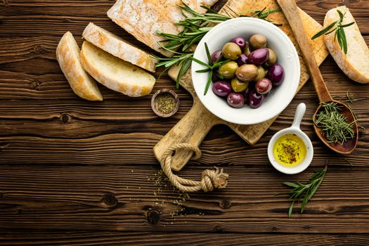 italian food ingredients, rosemary, olives, olive oil and ciabatta bread on wooden background