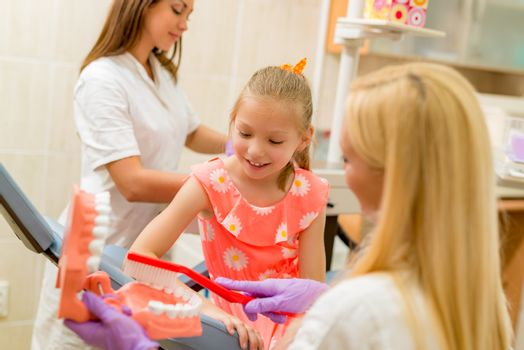 Dentist learning little girl patients how to brush her teeth with toothbrush. Selective focus. Focus on little girl.