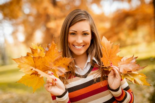 Cute young woman enjoying in sunny forest in autumn colors. She is holding golden yellow leaves and looking at camera.