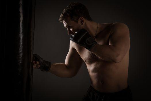 Young muscular man punching the boxing bag.