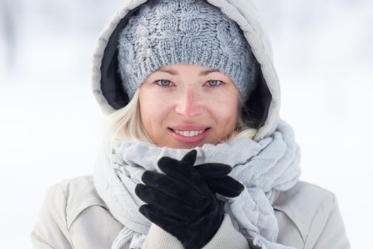 Girl wearing gloves, beeing cold outdoors in winter. Beautiful winter portrait of young woman in the winter snowy scenery.