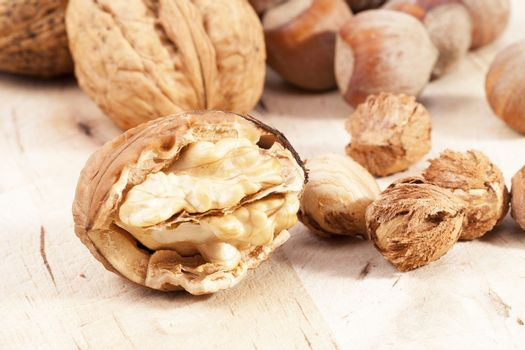 Composition of hazelnuts and walnuts on wooden plank