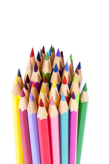 Chipped colored crayons on white background, close up