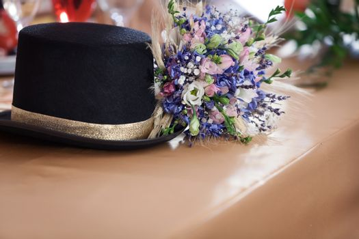 Vintage hat and a blue flower bouquet on a table.