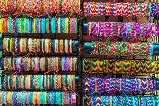 Various colorful woven and leather bracelets on sale at a street market