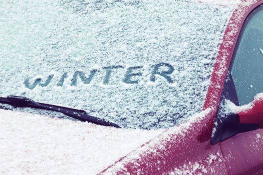Word Winter written on a car windshield covered with fresh snow