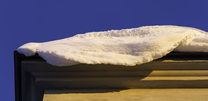 Snow on Edge of Roof with a clear blue sky.