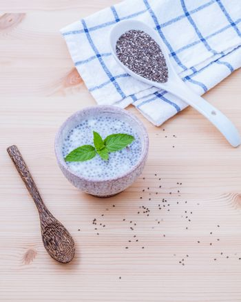 Nutritious chia seeds in ceramic bowl with wooden spoon for diet