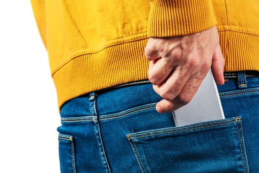 Hand reaching for the mobile phone in jeans back pocket