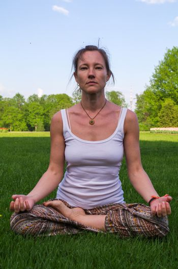 a young woman sitting in yoga lotus pose meditation outdoors