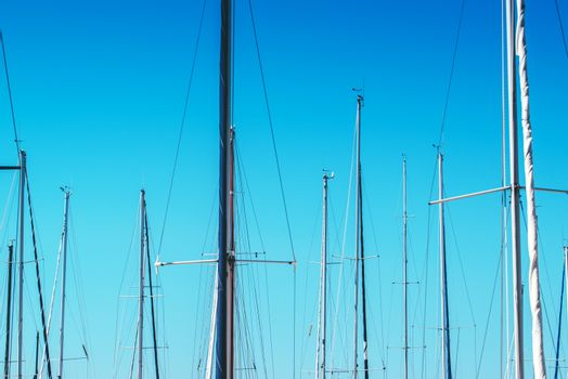 Sailboat masts in harbor against blue sky