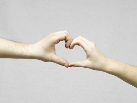Female and Male Hands Making a Heart Shape on a gray background.