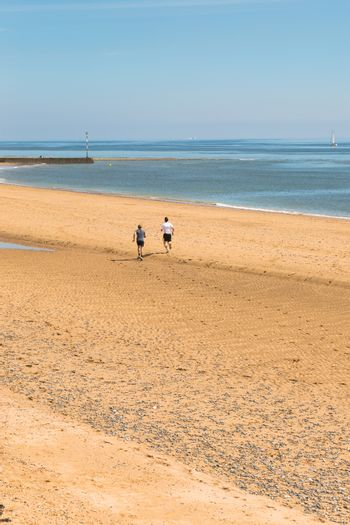 Two friends in sunny day run on gold beach at calm blue sea, sailboat in backgroud.