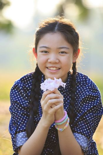 thai 12s years girl sitting on garden field with pink flowers in hand toothy smiling face happiness emotion