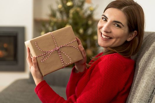 Beautiful happy woman at home holding Christmas presents