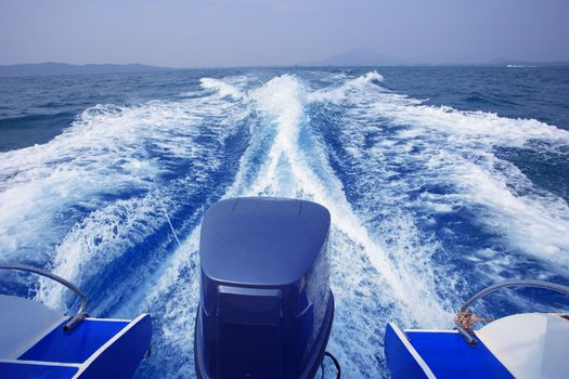 rear view of speed boat running high speed on blue sea water use for traveling to island destination