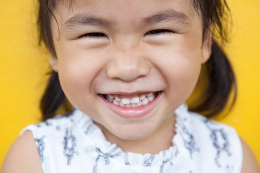 close up face of asian kid toothy smiling facial face with happiness emotion on yellow wall use for children lovely emotion and dental health theme