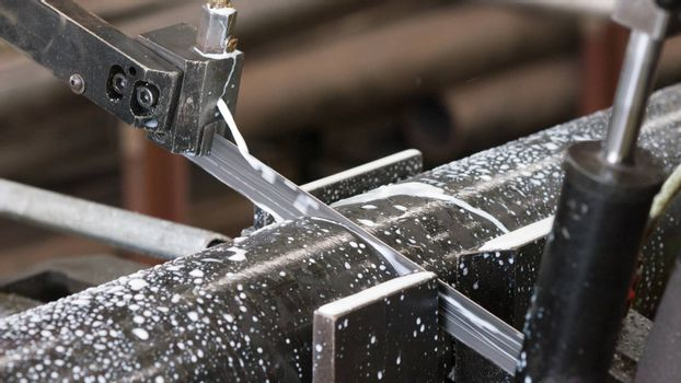 Industrial bandsaw with cooling liquid cutting a steel pipe. Shallow depth of field and motion blur.