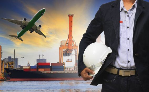 manager man holding safety helmet standing against ship and container on shipping port and cargo plane flying above use for freight and logistic transport industry