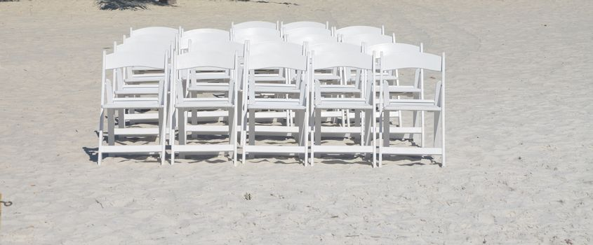 White chairs on the beach set up for a wedding.