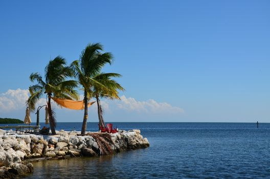 A sunny day and light breeze make this a quiet place to sit and enjoy the ocean in the florida keys. Two charis and a few palm trees complete the scene.