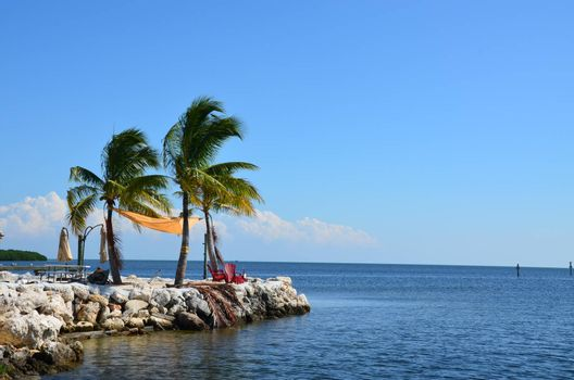 a spot on the edge of the island makes a quiet place to sit and enjoy the ocean in the florida keys. Two charis and a few palm trees complete the scene.