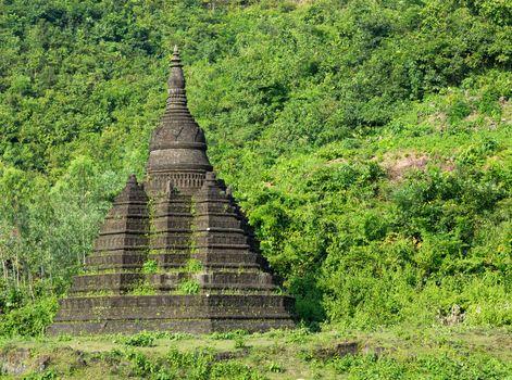 Small pagoda in Mrauk U, the Rakhine State of Myanmar, surrounded by lush foliage.