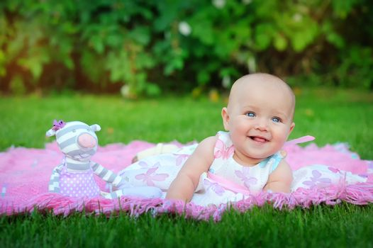 Baby lying on green grass in the park