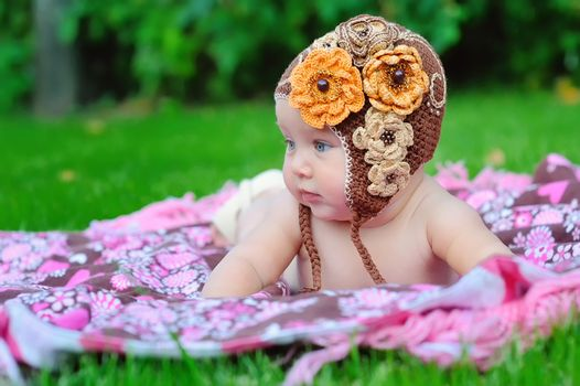 baby girl outdoors in a brown knitted cap