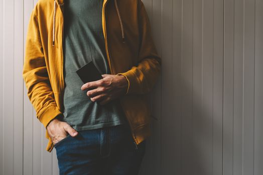 Casual young adult man posing with mobile phone in hand