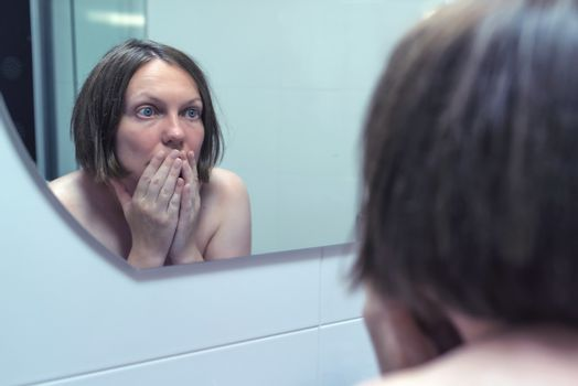Fear of getting old, adult female in front of mirror